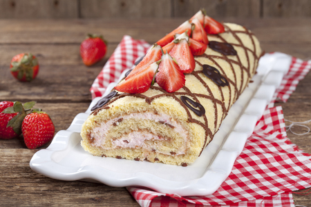 Homemade sponge roll with chocolate patterns, strawberries and cottage cheese cream on a wooden table with berries, selective focus