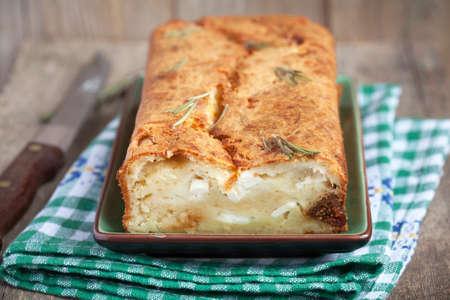 queso cabra: Torta del pan salado con queso parmesano, queso feta, los higos secos y romero en una mesa de madera en estilo rústico. enfoque selectivo.