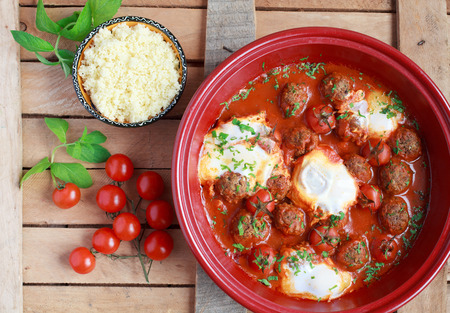 coo: Moroccan tagine of lamb with kefta (meatballs), tomatoes and eggs on a wooden table, selective focus