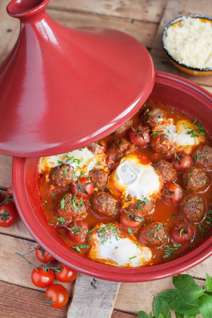 the lamb: Moroccan tagine of lamb with kefta meatballs, tomatoes and eggs on a wooden table, selective focus