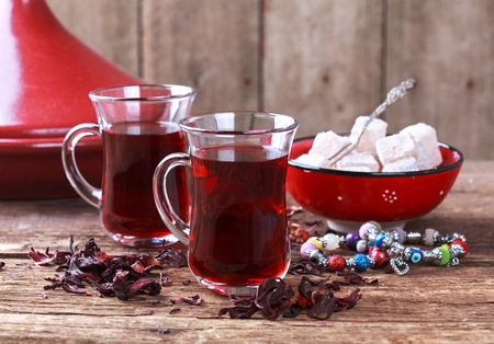 glass cup: The Turkish pomegranate tea in traditional glasses and turkish delight on wooden table, selective focus