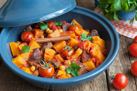 the lamb: Moroccan Tagine with beef, chickpeas,  pumpkin and cherry tomatoes on a wooden table. Selective focus