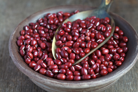 angularis: Dry red adzuki beans in a clay bowl on wooden table, selective focus - some beans in focus, some are not Stock Photo