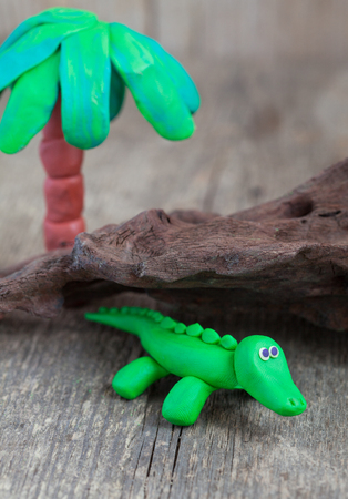 clumsy: Plasticine world - little homemade green crocodile with palm tree on a wooden background , selective focus Stock Photo