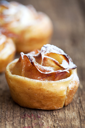 flaky: Roses made from puff pastry with petals of apple and cinnamon on a wooden table, selective focus