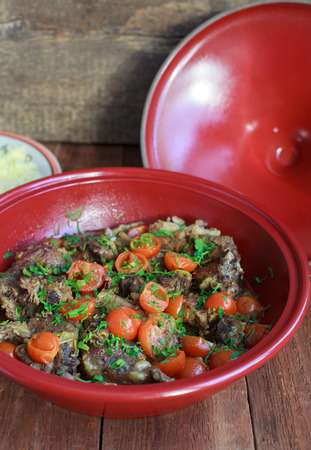 Moroccan tagine with lamb, tomatoes and couscous on a wooden table. Selective focus. Standard-Bild