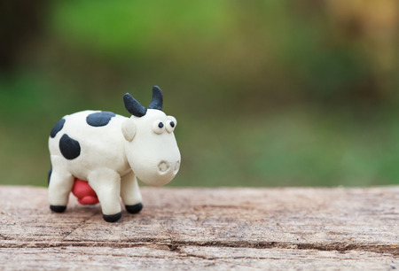 Plasticine world - little homemade black-and-white cow stands on a wooden floor on green background, selective focus