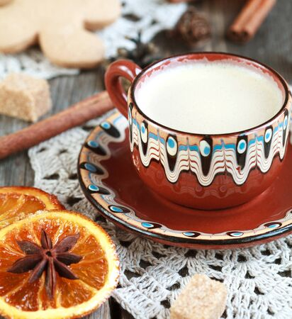 cinnamon sticks: Hot cocoa in a old ceramic cup on a wooden table with pieces of sugar, cinnamon sticks and candied orange slice. Selective focus, toned Stock Photo