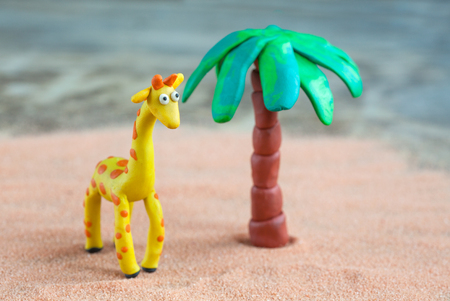 giraffa: Plasticine world - little homemade yellow giraffe with orange spots and palm on a wooden background, selective focus and place for text Stock Photo