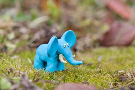 tusks: Plasticine world - little homemade blue elephant on a green background , selective focus and place for text Stock Photo