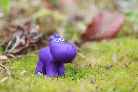 clumsy: Plasticine world - little homemade purple hippo on a green background, selective focus and place for text