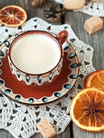 cinnamon sticks: Hot cocoa in a old ceramic cup on a wooden table with pieces of sugar, cinnamon sticks and candied orange slice. Selective focus on milk froth, toned Stock Photo