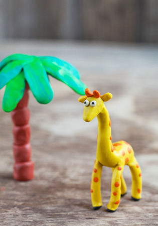 clumsy: Plasticine world - little homemade yellow giraffe with orange spots and palm on a wooden background, selective focus and place for text Stock Photo