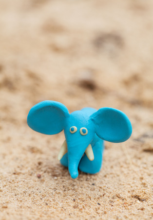 tusks: Plasticine world - little homemade blue elephant on a sand background , selective focus and place for text Stock Photo