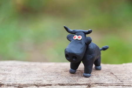 red eyes: Plasticine world - little homemade black bull with red eyes stands on a wooden floor on green background, selective focus