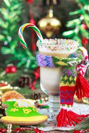 caballo bebe: Un vaso de caf� con leche caliente con una peque�a bufanda de punto y pan de jengibre de Navidad caseras pintadas como un caballo verde, y la decoraci�n festiva en el fondo de madera. Atenci�n selectiva y el lugar de texto.