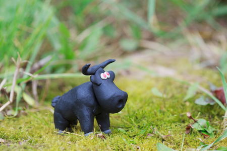 red eyes: Plasticine world - little homemade black bull with red eyes on green background, selective focus