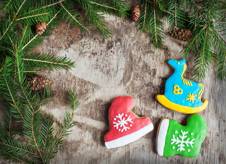 wooden hat: Homemade christmas gingerbreads painted as a blue horse, a red hat and green boot on the wooden background with fir branches. Selective focus and place for text. Toned Stock Photo