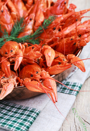 deepening: Copper frying pan with red boiled crawfish on a wooden table in rustic style, close-up, selective focus on some crawfish Stock Photo