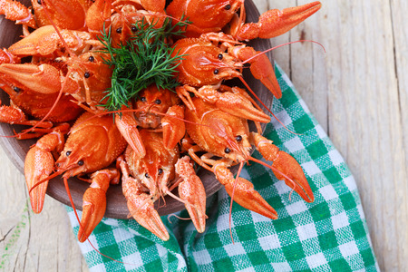 deepening: Old bowl with red boiled crawfish on a wooden table in rustic style, close-up, selective focus on some crawfishes