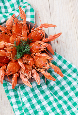 deepening: Old bowl with red boiled crawfish on a wooden table in rustic style, close-up, selective focus on some crawfishes. Place for text
