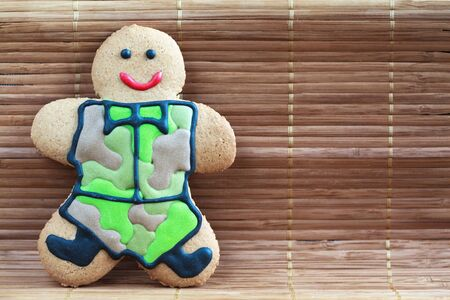 defender: Homemade Gingerbread men in protective khaki uniforms on Defender of the Fatherland Day, close up, place for text