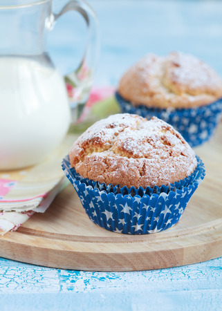 edibles: Close-up of two homemade orange muffins with a jug of milk, selective focus