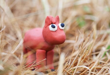 hay: Plasticine world - little homemade red horse stands in the hay, selective focus on head