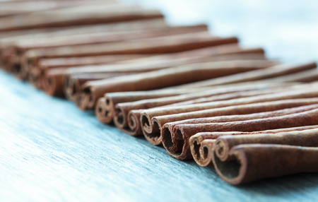 cannelle: row of cinnamon sticks on an old wooden table background with place for text, selective focus on the third stick
