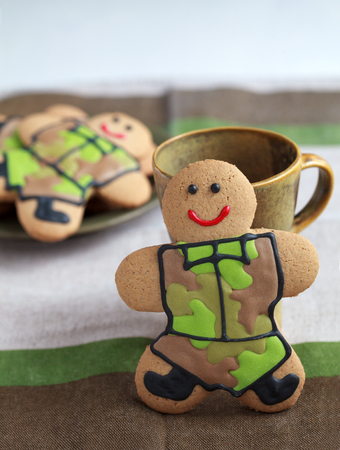 defender: Homemade Gingerbread men in protective khaki uniforms on Defender of the Fatherland Day, selective focus Stock Photo