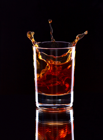 Glass of whiskey with splash on dark background, selective focus on the glass Stockfoto