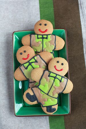 defender: Gingerbread men in protective khaki uniforms on Defender of the Fatherland Day, selective focus