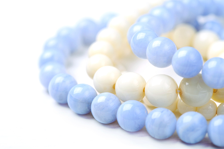 nicety: bead necklace made from blue agate and white coral on a white table, close-up, selective focus on some beads
