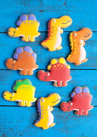 decorating: Homemade gingerbread cookie in the shape of dinosaurs on a wooden background. Space for text and selective focus.