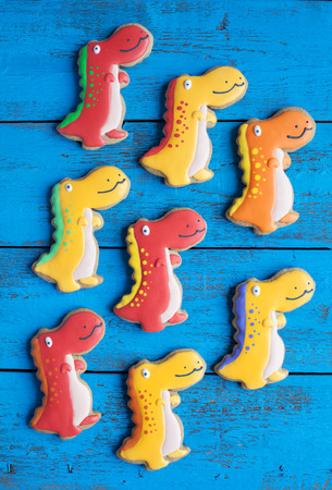 dinosaur: Homemade gingerbread cookie in the shape of dinosaurs on a wooden background. Space for text and selective focus.