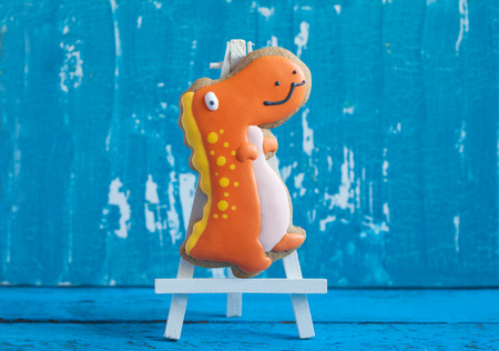 dinosaurio: Galleta de jengibre hecha en casa en forma de dinosaurios en un fondo de madera. Espacio para el texto y el enfoque selectivo. Foto de archivo