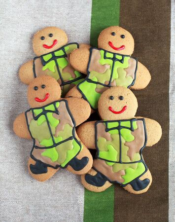 defender: Homemade Gingerbread men in protective khaki uniforms on Defender of the Fatherland Day, selective focus the right man