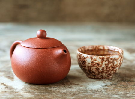 chinese tea ceremony: Traditional chinese tea ceremony accessories: tea pot, cup on the wooden table, selective focus, toned Stock Photo