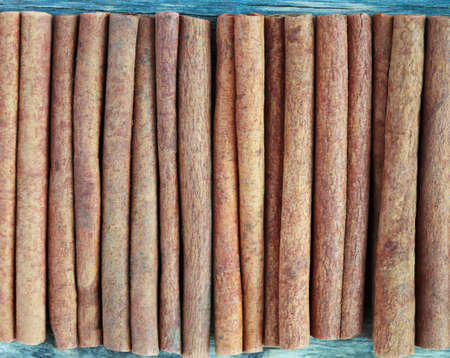 cannelle: cinnamon sticks on an old wooden table background with place for text, selective focus