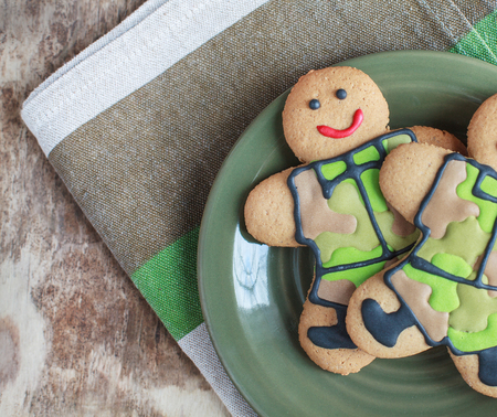 Two homemade Gingerbread men in protective khaki uniforms on Defender of the Fatherland Day, selective focus on left man, place for text
