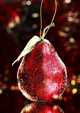 gewgaw: Christmas decoration, red pear on a bright red tinsel, selective focus on pear