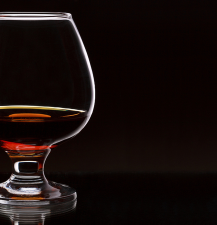 liquor glass: Glass of whiskey with bottle, on dark background, selective focus on the glass with place for text