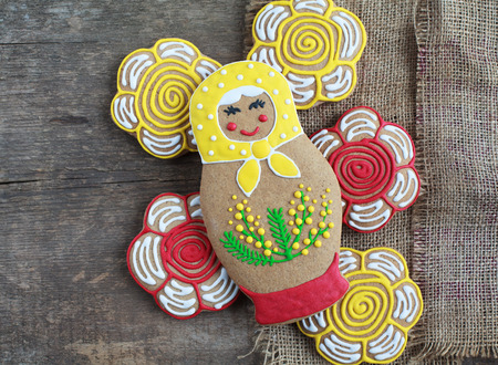 russian nesting dolls: Edible homemade gingerbread as a traditional Russian nesting dolls - matryoshka, on the wooden table with flowers and place for text