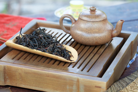 tea table: Traditional chinese tea ceremony accessories (tea pot and Feng Huang Puer tea) on the tea table
