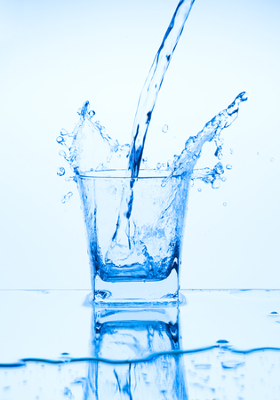Splash from pouring blue water into the glass on a light blue background