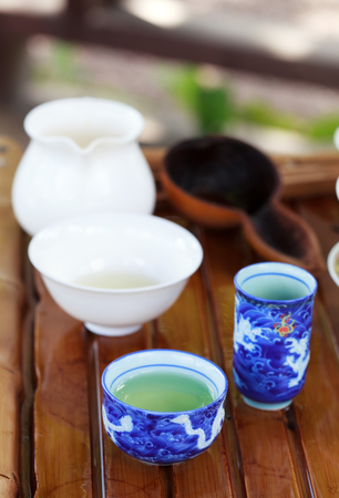 tea table: Traditional chinese tea ceremony accessories (tea cups) on the tea table, selective focus