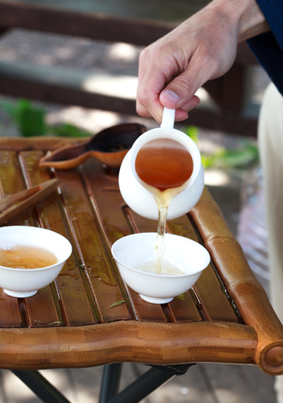 chinese tea ceremony: Traditional chinese tea ceremony accessories cups, pouring tea on the tea table, selective focus