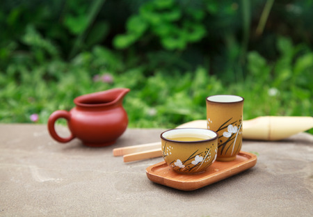 Traditional chinese tea ceremony accessories tea cups and pitcher on the stone table, selective focus on cup