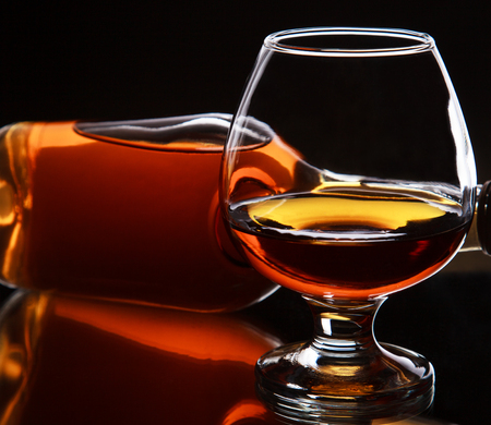 Glass of whiskey with bottle, on dark background, selective focus on the whiskey in glass