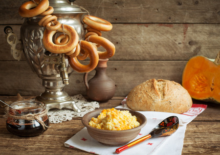 Russian rustic still life: a samovar with bagels, millet porridge with pumpkin, homemade bread and cherry jam. Selective focus.